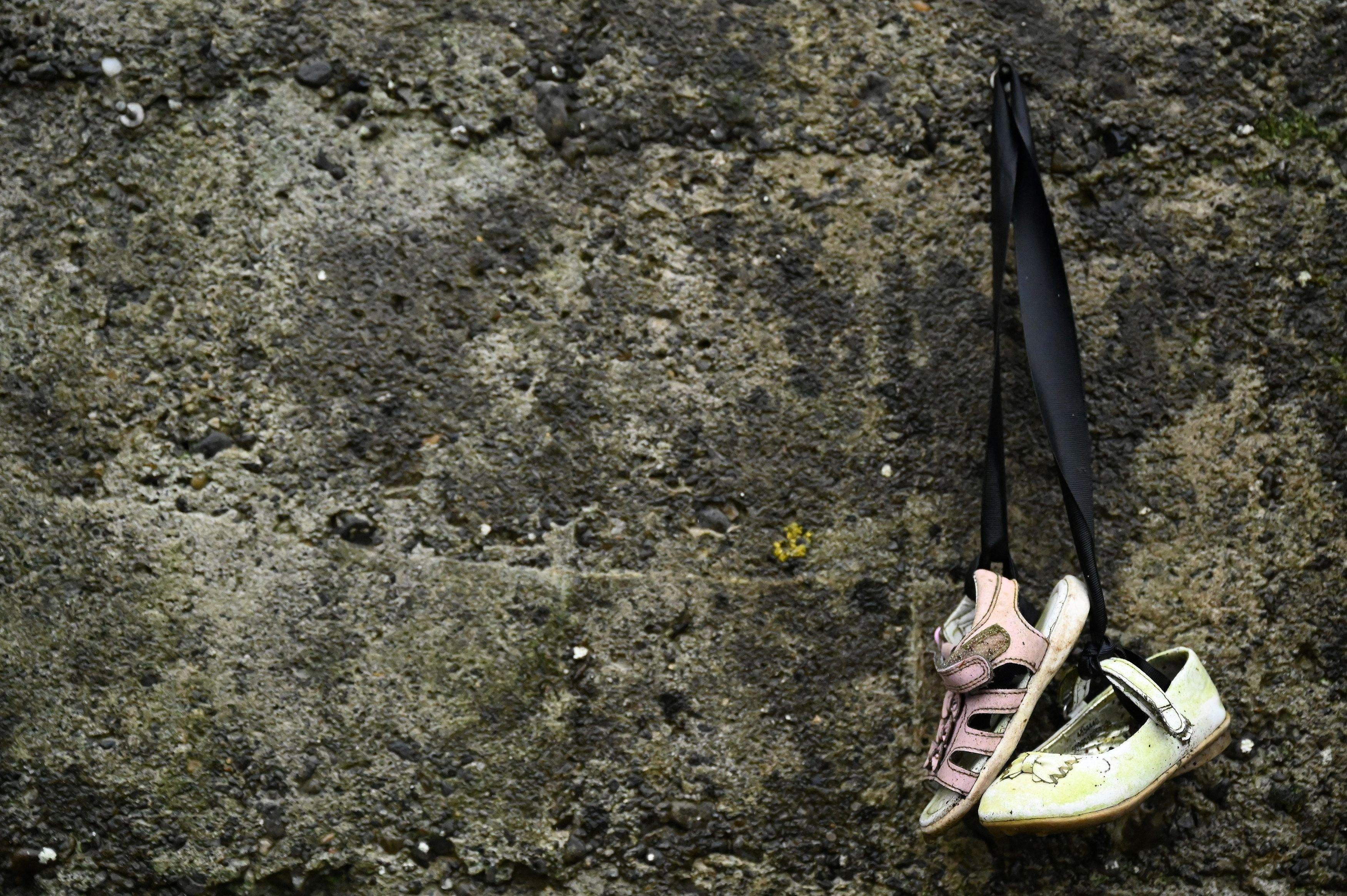 Unos zapatos colgados en el muro en recuerdo a los niños fallecidos