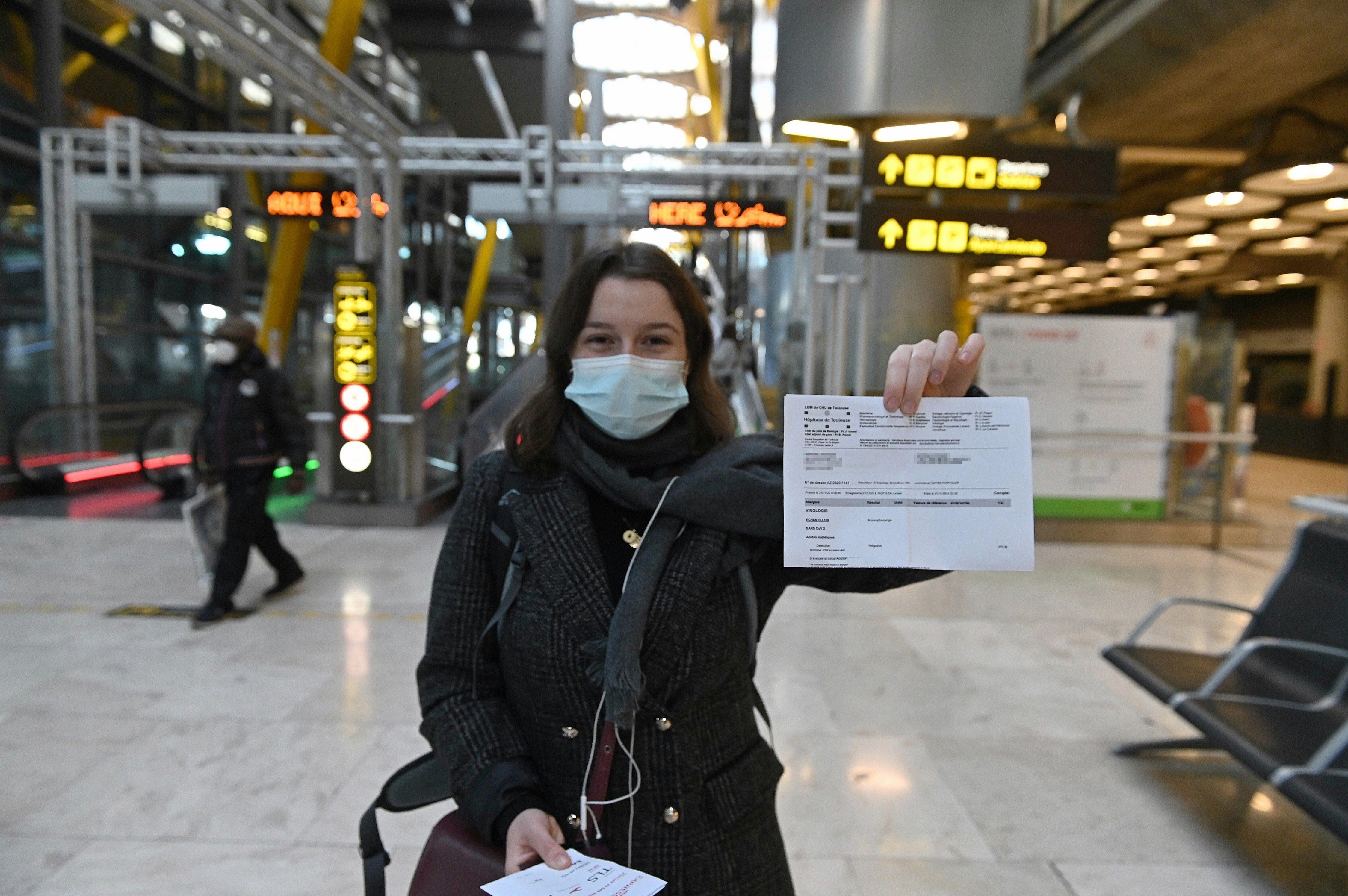Una joven muestra el resultado de su PCR a su llegada al aeropuerto Adolfo Suárez-Barajas en Madrid, este lunes