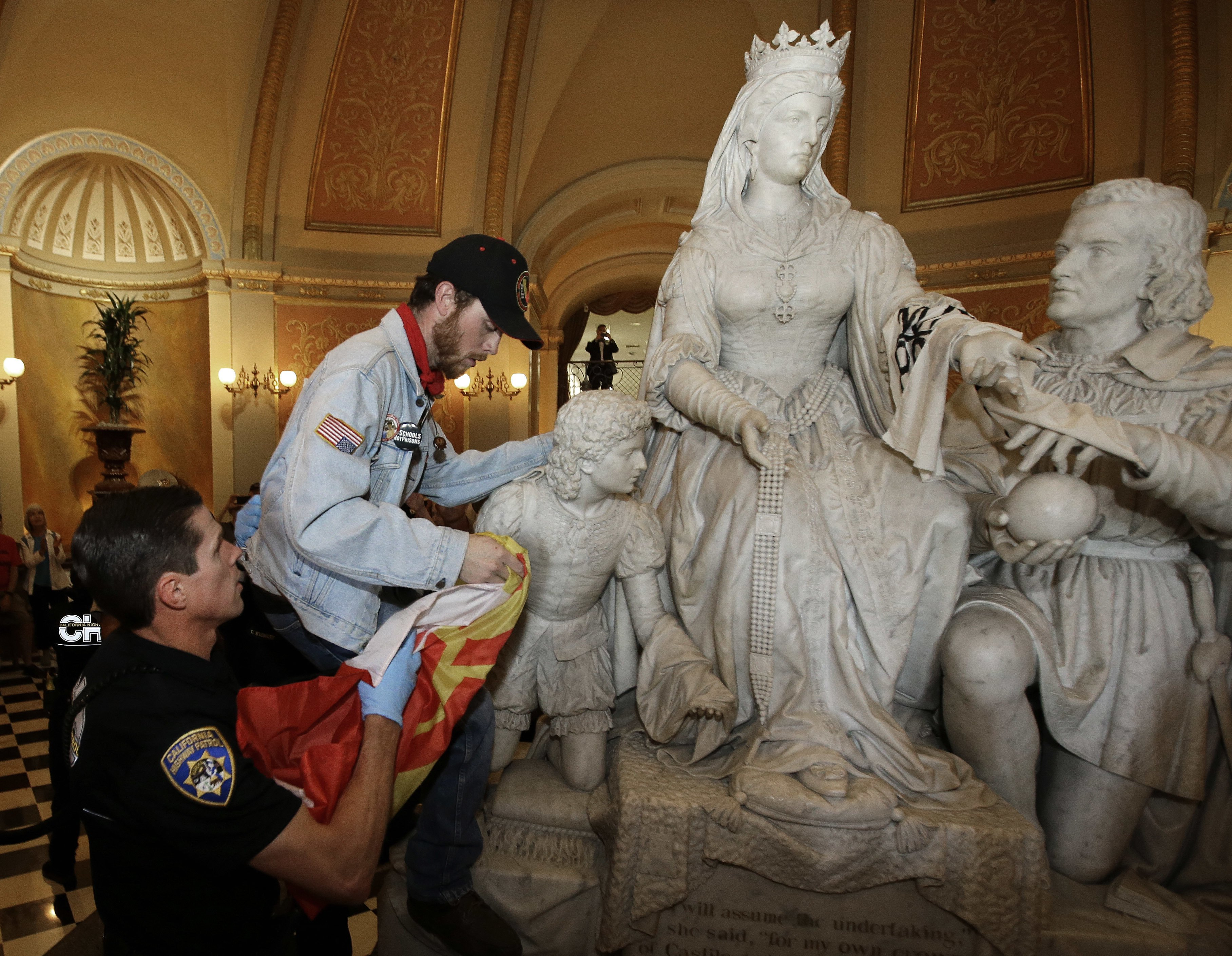 """FILE — In this June 4, 2018, file photo a demonstrator is removed from the statue of Queen Isabella and Christopher Columbus in the rotunda of the Capitol, by a California Highway Patrol officer, during a protest in Sacramento, Calif. Calling Columbus """"a deeply polarizing historical figure,"""" Senate President Pro Ten Toni Atkins, D-San Diego; Assembly Speaker Anthony Rendon, D-Lakewood; and Assembly Rules Committee Chairman Ken Cooley, D-Rancho Cordova, announced Tuesday, June 16, 2020, that the controversial statue will be removed. (AP Photo/Rich Pedroncelli, File)"""