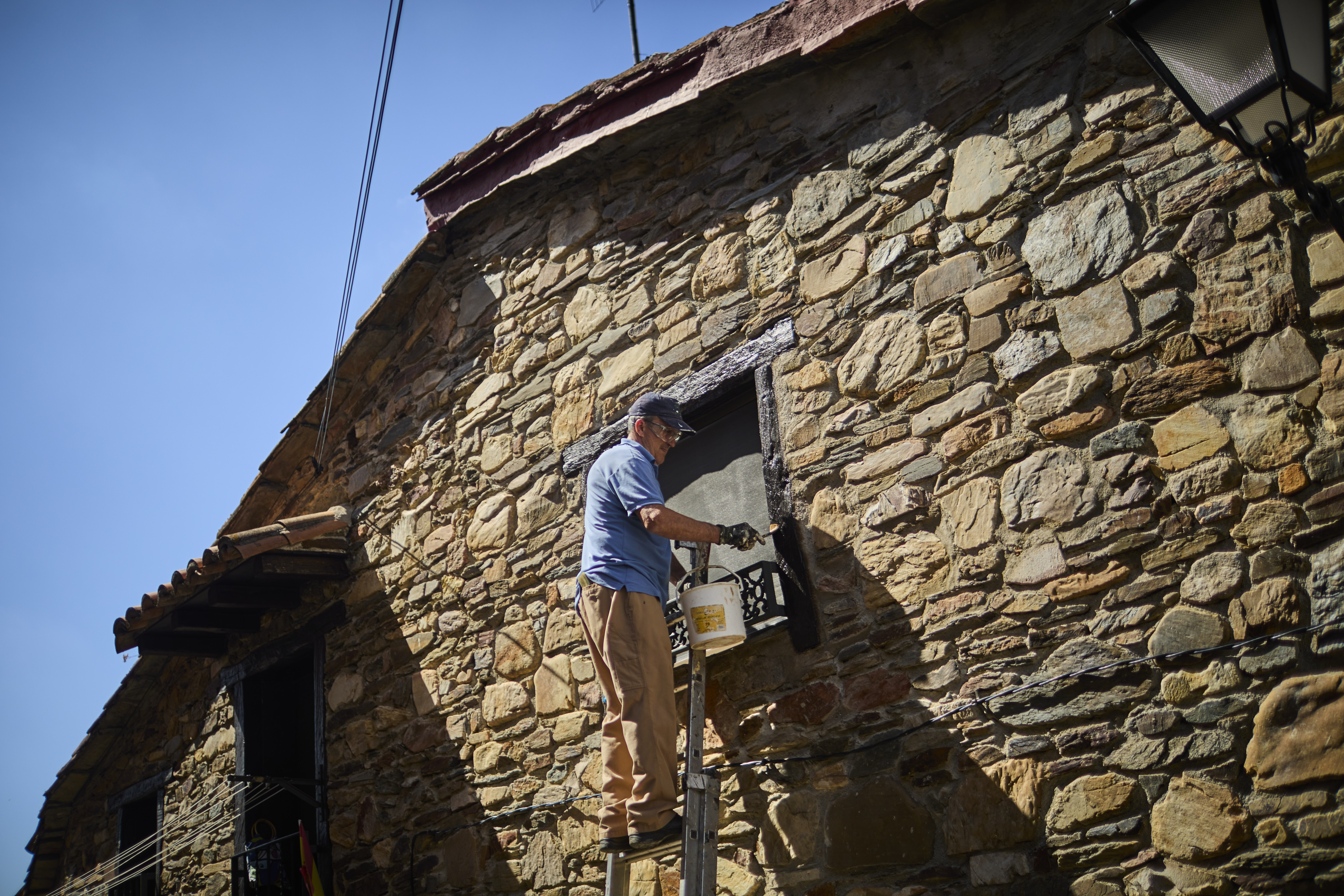 Un vecino arregla la fachada de su vivienda en Puebla de la Sierra, a 110 km del Madrid capital