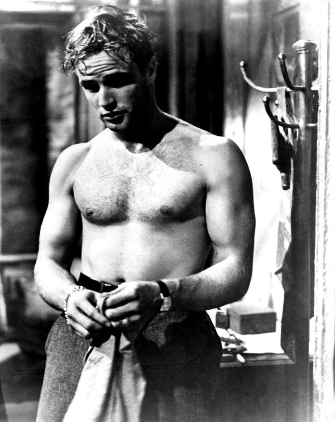 El torso desnudo de Marlon Brando (Nebraska, 1924) no fue el primero. La audiencia había visto ya hombres descamisados en el cine, claro: eran necesarios en los filmes de aventuras de los treinta y los cuarenta. Pero en 'Un tranvía llamado deseo' (Elia Kazan, 1951), Brando inventó al macarra deseable y desvergonzado, el que es capaz de erotizar a una profesora acomplejada solo con llegar a casa y quitarse su camiseta sucia. Marlon regaló al cine el perfil de chico joven y fibrado pero cuyos músculos no eran producto de la lucha y la fuerza, sino de una vida dura. Brando no conocía el gimnasio, tan solo el melodrama vital.