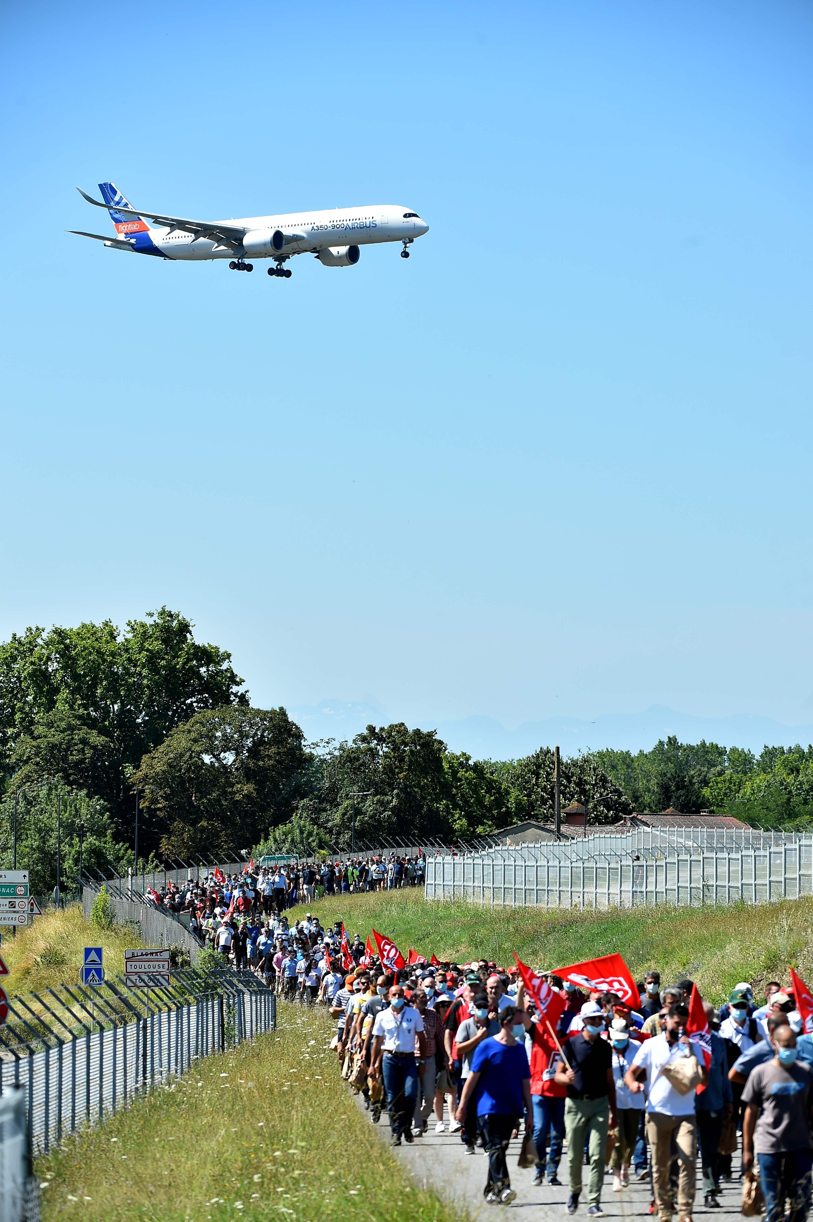 Empleados de Airbus se manifiestan por los despidos masivos junto a una pista del aeropuerto de Toulouse-Blagnac.