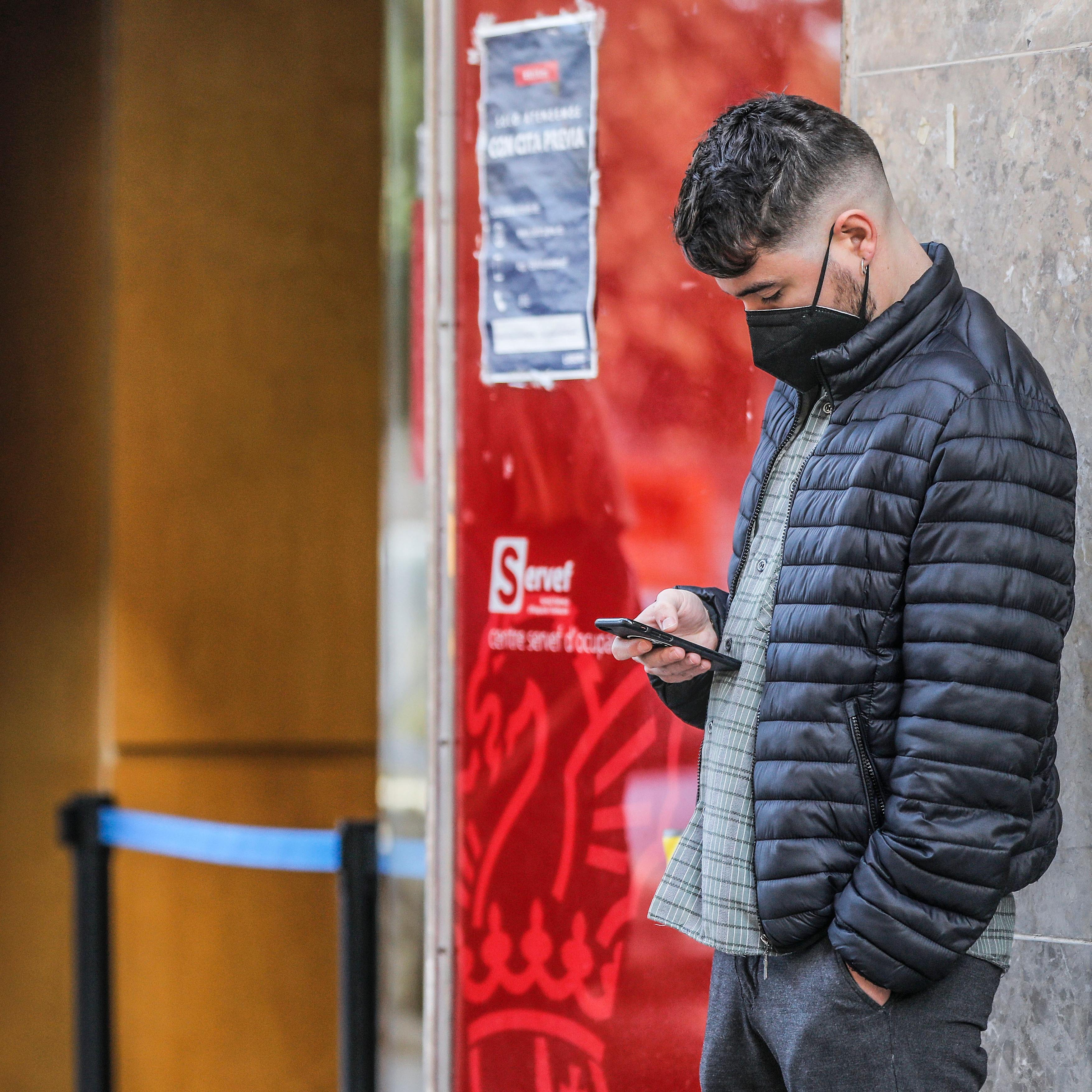 Un joven mira su teléfono móvil mientras espera para entrar en una oficina del SEPE (antiguo INEM), en Valencia, Comunidad Valenciana (España), a 12 de febrero de 2021. El número de parados registrados en las oficinas de empleo en la Comunitat Valenciana subió en 10.094 personas en enero, lo que supone un 2,3% más que en diciembre de 2020, más que el repunte medio del 1,9%. Además, hubo 81.233 parados menos en la Comunitat, un 22,16% más en relación con enero de 2020. 12 FEBRERO 2021;CITA PREVIA;VALENCIA;PARO;EMPLEO;DESEMPLEO;INEM Rober Solsona / Europa Press 12/02/2021